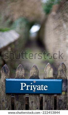 Blue privacy sign on a rustic fence
