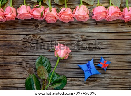 Blue, red and white various Valentines Day bowed gift boxes over worn out wooden background with roses on top - stock photo