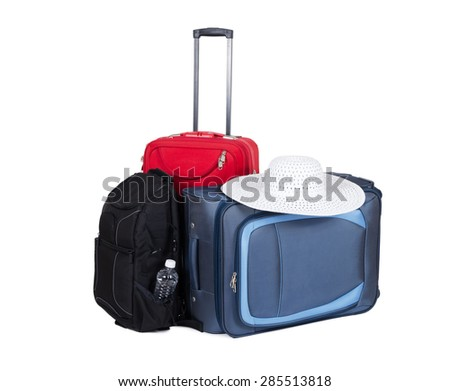 Blue, red travel suitcases and black backpack isolated on white background