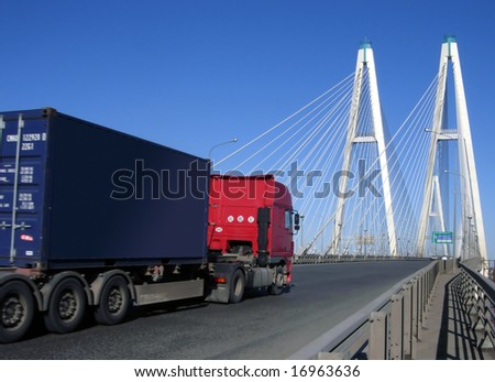 blue-red truck driving on cable-braced bridge - stock photo