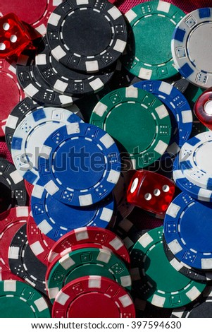 Blue, red, white, green and black poker chips and red dice. Many color poker chips and red dice background.