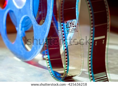 Blue reel of film on a light background - stock photo