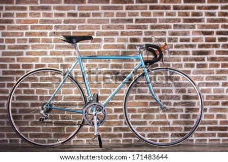 Blue retro bicycle on red brick wall background