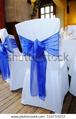 Blue ribbon chair cover tied in bow at wedding reception