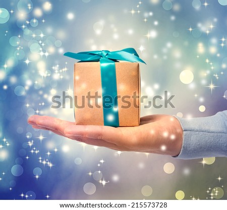 Blue ribbon present box on a hand over blue shiny background - stock photo