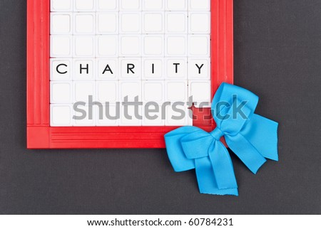 Blue Ribbon with Square Puzzle and Word Charity in Tiles - stock photo