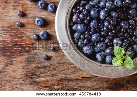 Blue ripe blueberries in a metal plate.  wooden background.