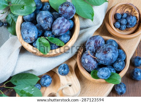 Blue ripe plums with green leaves in different wooden bowls - stock photo