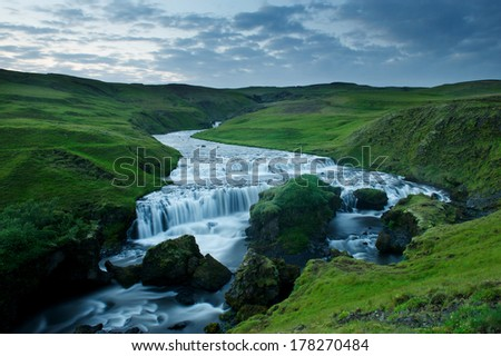 Blue river captured with long exposure among green hills in South Iceland near Skogafoss waterfall - stock photo