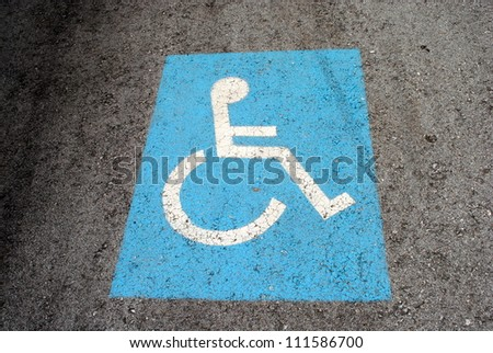 blue road marking for disabled and invalid parking - stock photo
