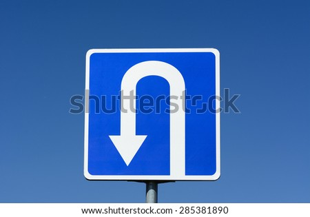 Blue road sign with U Turn traffic sign with blue sky background - stock photo