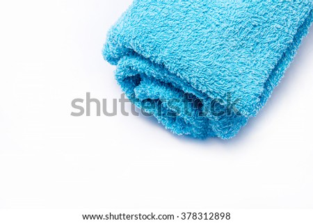 Blue rolled up towel on white background. - stock photo