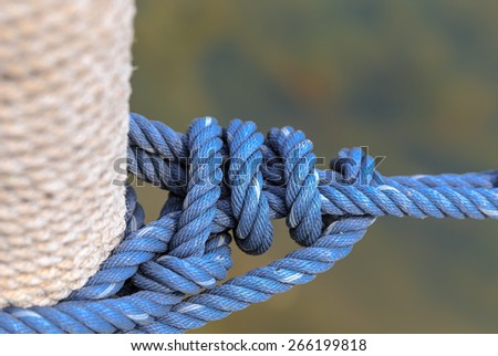 blue rope tied up the pole in nature backgrond - stock photo