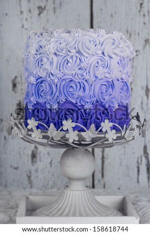 blue rosette cake on cake stand - stock photo