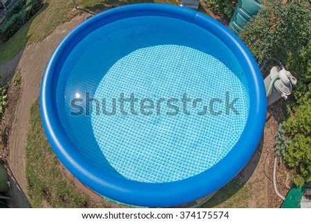 Blue round rubber pool in the garden - stock photo