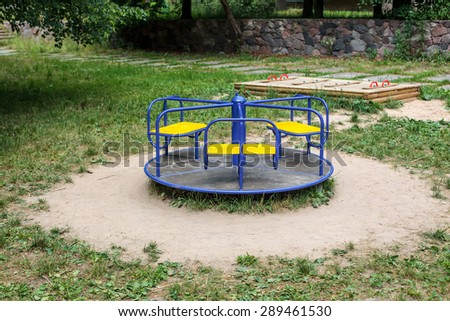 Blue roundabout in empty playground - stock photo