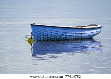 Blue Rowing Boat anchored near Carsthorn (UK OS Ref.NX 994 597) at high tide on a flat calm sunny day July 2007 - stock photo