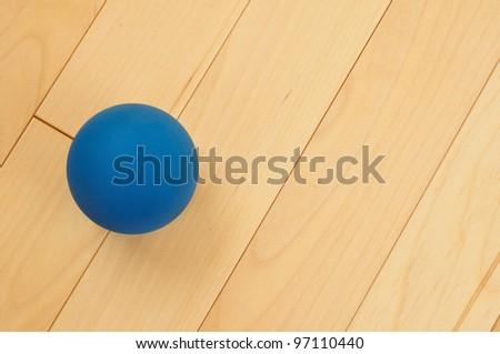 Blue Rubber Racquetball on Hardwood Court Floor - stock photo