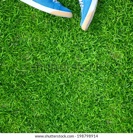 blue rubber sneakers on saturated green grass