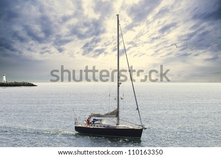 blue sailboat leaving the harbor - stock photo