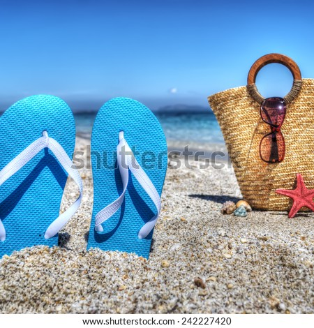 blue sandals and straw bag by the shore in hdr - stock photo
