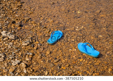 Blue sandals near the  river - stock photo