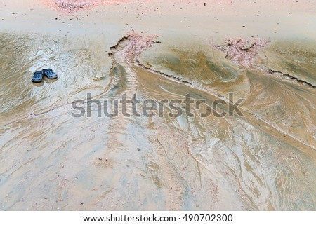 Blue sandals outside alone next to erosion in the sand at a remote beach