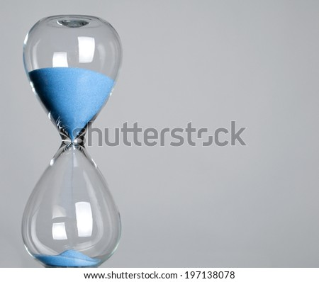 Blue sands of time trickling through to the other side of the transparent hourglass.