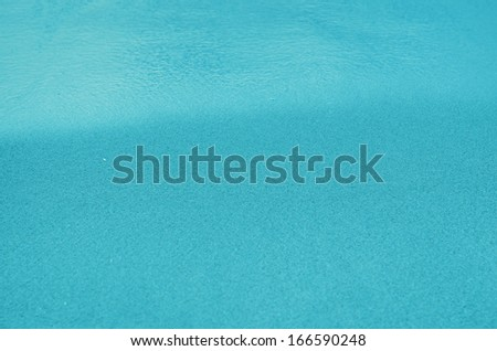 Blue Sandy beach background. Detailed sand texture and water . Top view - stock photo