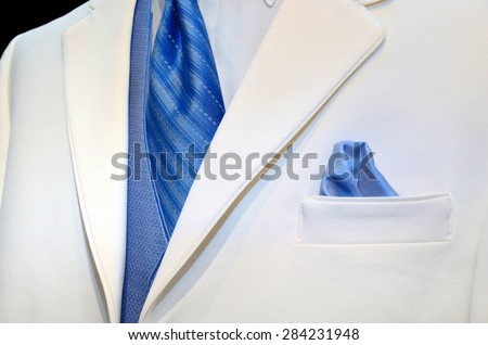 blue satin tie, vest and handkerchief in pocket accenting a white tuxedo - stock photo