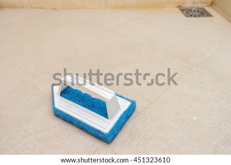 blue scrub brush on the bathroom floor