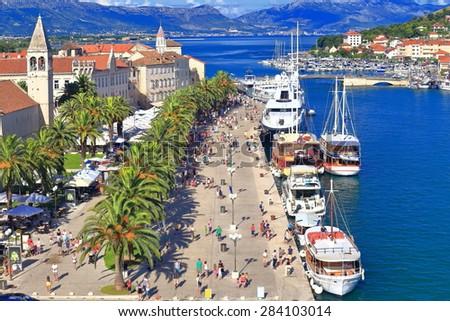 Blue sea along sunny pier and Venetian town, Trogir, Croatia - stock photo