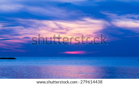 Blue sea and calmly wave at sunrise, a little tidal. Sun just come up. Glittering reflection from sunlight on sea surface.  - stock photo
