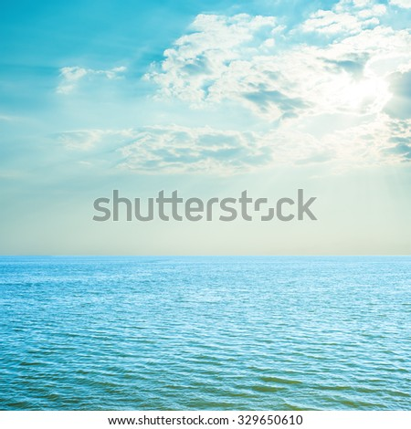 blue sea and cloudy sky over it. sunset time - stock photo
