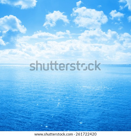 Blue sea and sky with white clouds. - stock photo