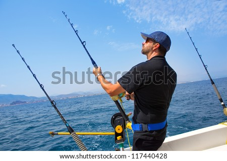 blue sea fisherman in trolling boat in action with downrigger and rod - stock photo