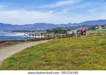 Blue sea, sky & white clouds, young couple holding hands on a walking / path near the beach, at the Fiscalini Ranch Preserve on the Big Sur coast, California Central Coast, near Cambria CA. - stock photo