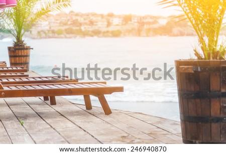 blue Sea sunbeds greens plants - stock photo