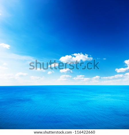 Blue sea under clouds sky - stock photo