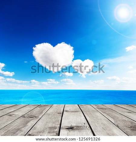 Blue sea under clouds sky with heart shape cloud and wooden pier. Valentine background