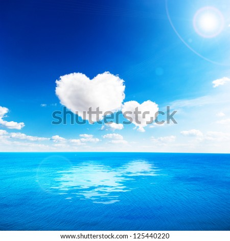 Blue sea under clouds sky with heart shape cloud. Valentine background - stock photo