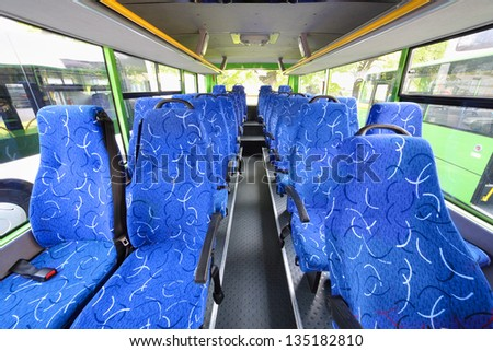 Blue seats for passengers in saloon of empty city bus with grey floor.