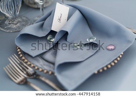 Blue serviette coveres with decorative stones lie over a glass dinner plate
