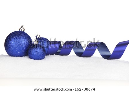 Blue shiny Christmas balls and ribbon on snow - stock photo