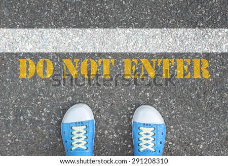 Blue shoes standing at the line 'do not enter'. It is the end. Crossing to line is prohibit, not allow, restricted. - stock photo