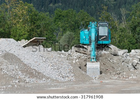 blue shovel digger on gravel heap in front of forest - stock photo