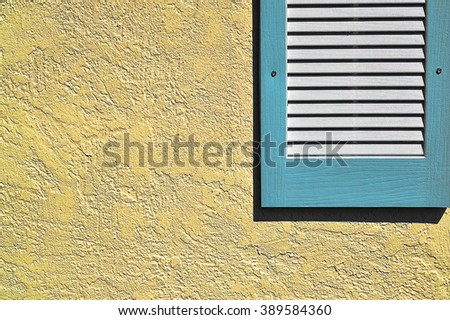 Blue shutter on yellow stucco exterior wall - stock photo
