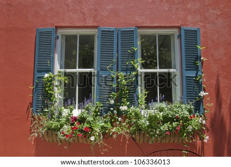 Blue shuttered windows in the orange stucco wall of an eighteenth century house.
