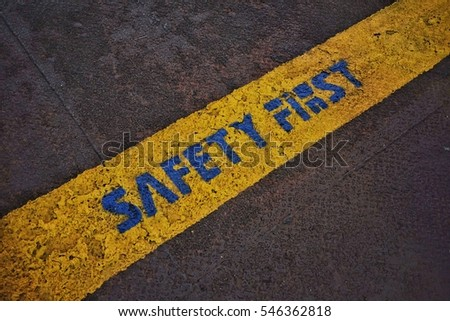 Blue sign of safety first on yellow line background on steel floor.