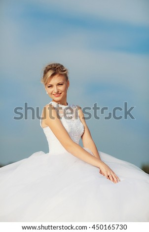 Blue sky and a charming bride - stock photo